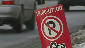An overnight parking ban sign sits in a snow bank while a vehicle drives by on an Ottawa street in this undated photo.