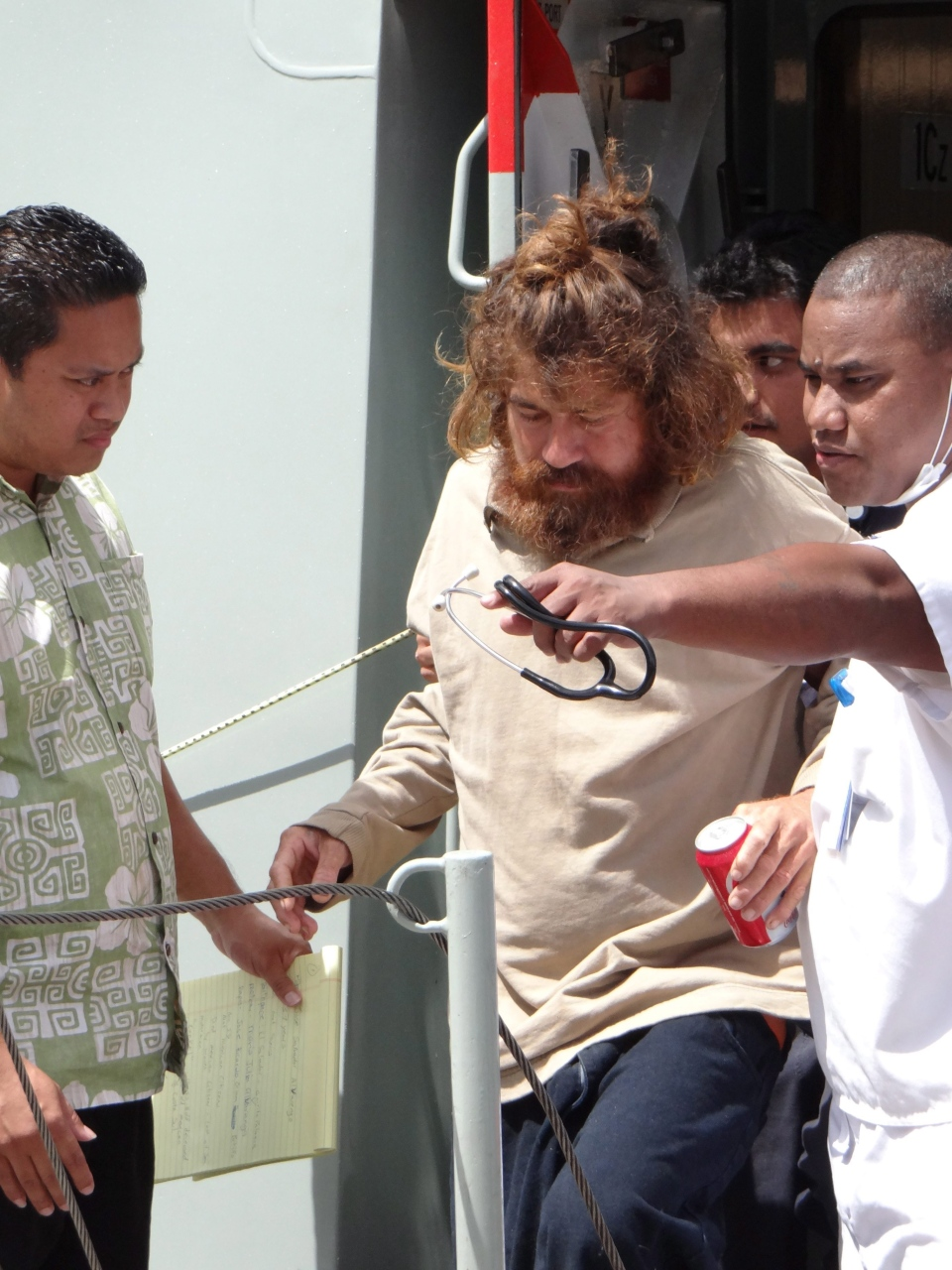 A man who identifies himself as Jose Salvador Alvarenga, centre, gets off a ship in Majuro, the Marshall Islands, after he was rescued from being washed ashore on the tiny atoll of Ebon in the Pacific Ocean, Monday, Feb. 3, 2014. (AP / Marshall Island Journal)