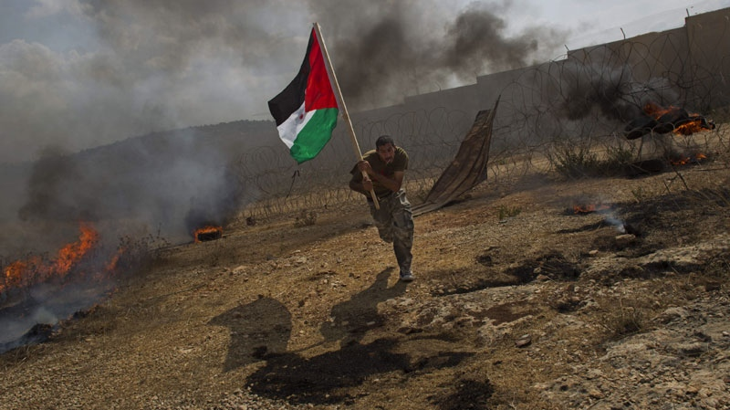 Palestinian Ashraf Abu Rahma runs away from tear gas fired by Israeli troops, not pictured, during a demonstration in the West Bank town of Bilin, near Ramallah, Friday, Sept. 9, 2011. (AP Photo/Bernat Armangue)
