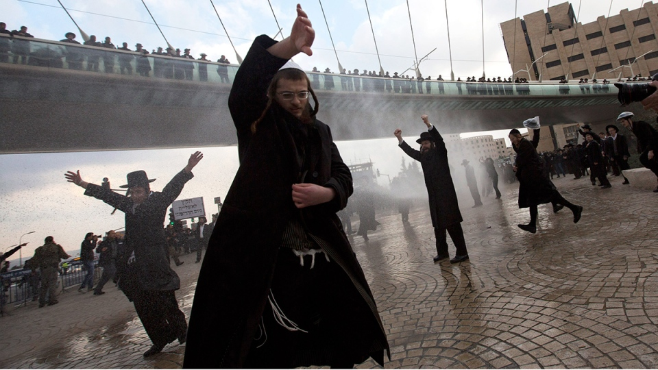 Police officers shoot a water cannon at ultra-Orthodox Jewish men during their demonstration in Jerusalem, Thursday, Feb. 6, 2014. (AP / Sebastian Scheiner)