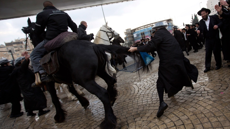 Israeli police officers on horses disperse a crowd of ultra-Orthodox Jewish men during a demonstration in Jerusalem, Thursday, Feb. 6, 2014. (AP / Sebastian Scheiner)
