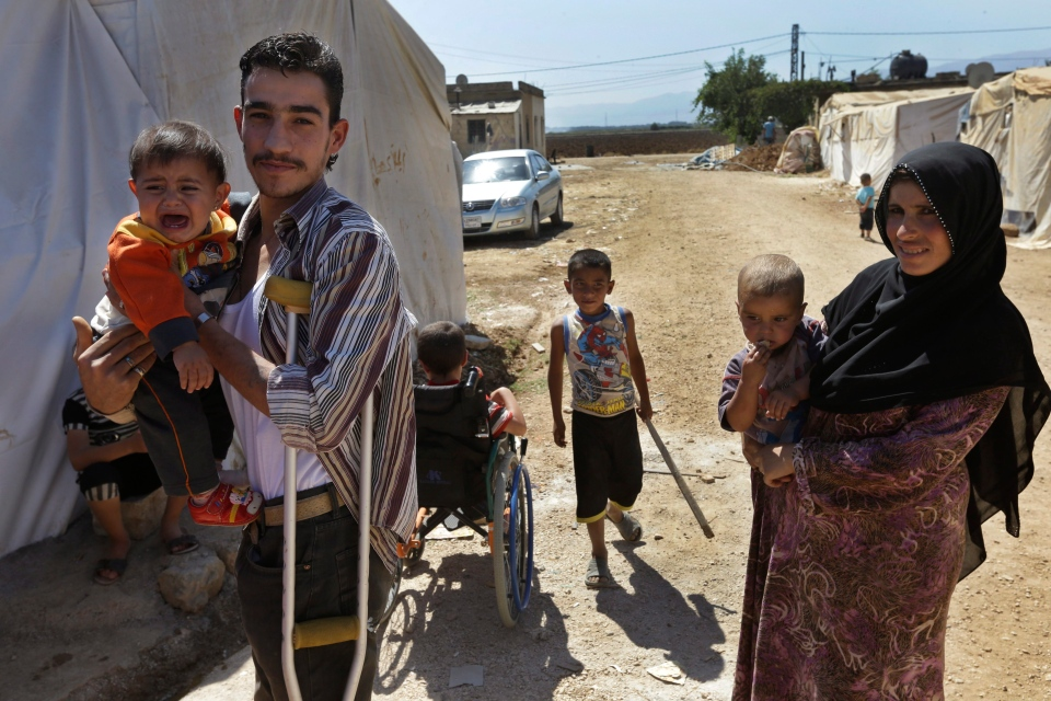 Syrian refugee Mohammed Ahmed, 20, right, who fled his home with his family from Baba Amro, Homs province, carries his son at a temporary refugee camp, in the eastern Lebanese Town of Al-Faour, Bekaa Valley near the border with Syria, Lebanon on Wednesday, Sept. 11, 2013. (AP / Hussein Malla)
