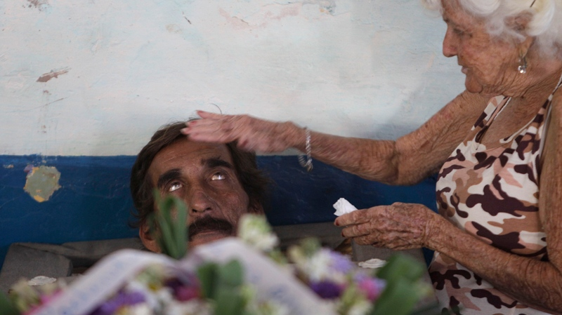 In this Feb. 5, 2014 photo, Divaldo Aguiar, who plays the part of Pachencho, in a mock funeral known as the Burial of Pachencho, lies inside a coffin as Carmen Zamora, who plays the part of his widow, puts her hand on his head, at a cemetery in Santiago de Las Vegas, Cuba. (AP Photo/Franklin Reyes)