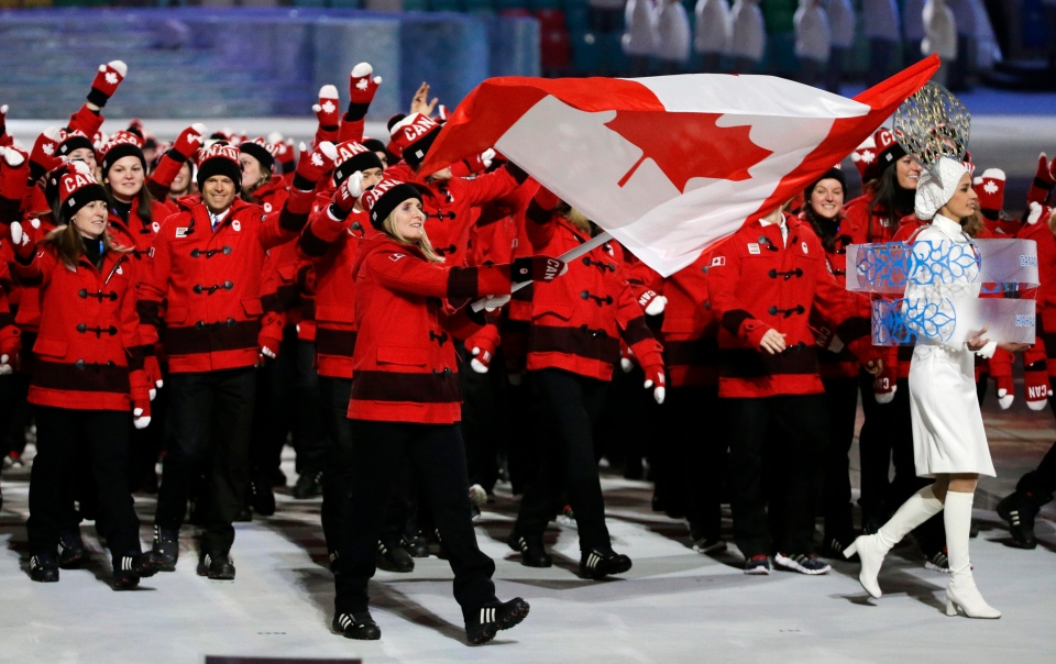 Hayley Wickenheiser of Canada carries the national flag as she leads the team during the opening ceremony of the 2014 Winter Olympics in Sochi, Russia, Friday, Feb. 7, 2014. (AP / Mark Humphrey)