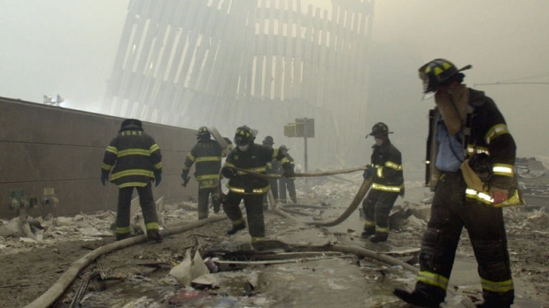 With the skeleton of the World Trade Center twin towers in the background, New York City firefighters work amid debris on Cortlandt St. after the terrorist attacks Tuesday, Sept. 11, 2001. (AP / Mark Lennihan)