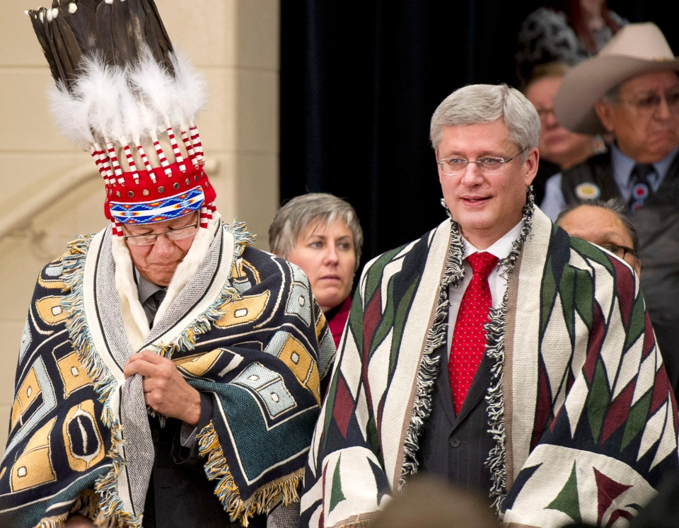 Prime Minister Stephen Harper, right, and Blood Reserve Grand Chief Charles Weaslehead wear ceremonial blankets after Harper made an announcement on First Nations Education in Stand Off, Alberta on Friday, February 7, 2014. (Larry MacDougal / THE CANADIAN PRESS)