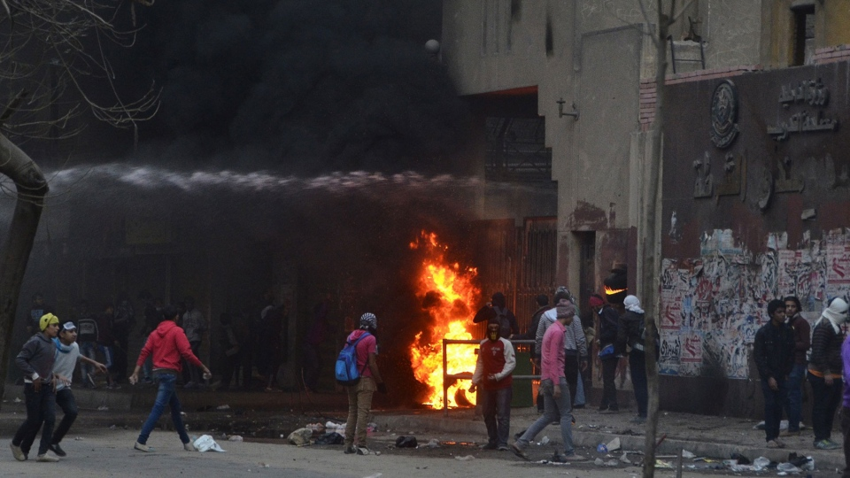 Supporters of Egypt's ousted President Mohammed Morsi damage a police building as water canon from the building is used to extinguish flames in Cairo's Ain Shams district, Egypt, Friday, Feb. 7, 2014. (AP / Mostafa Darwish)