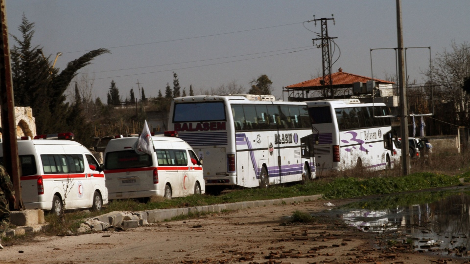 Some Syrian people on two buses followed by the Syrian Arab Red Crescent's vehicles evacuate Syria's battleground city of Homs, Friday, Feb. 7, 2014. (AP)