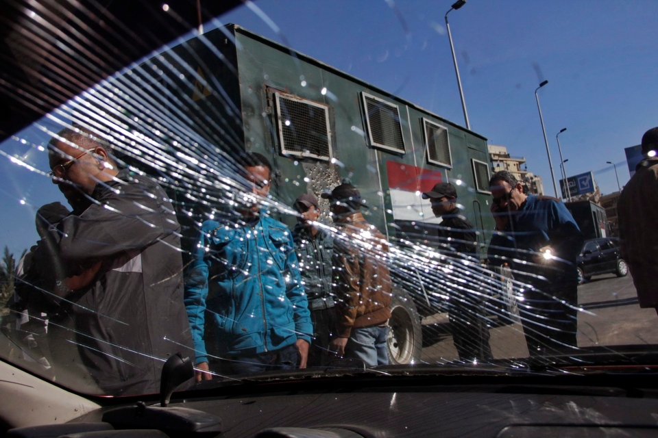 Egypt's security forces look through the shuttered windshield of a vehicle damaged after bomb explosions targeted at a checkpoint in Giza, Egypt, Friday, Feb. 7, 2014. (AP / El Shorouk, Aly Hazzaa)
