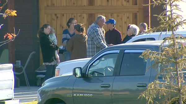 Family and friends are seen standing outside a home in Sparwood, B.C., Sunday, Sept. 11, 2011.