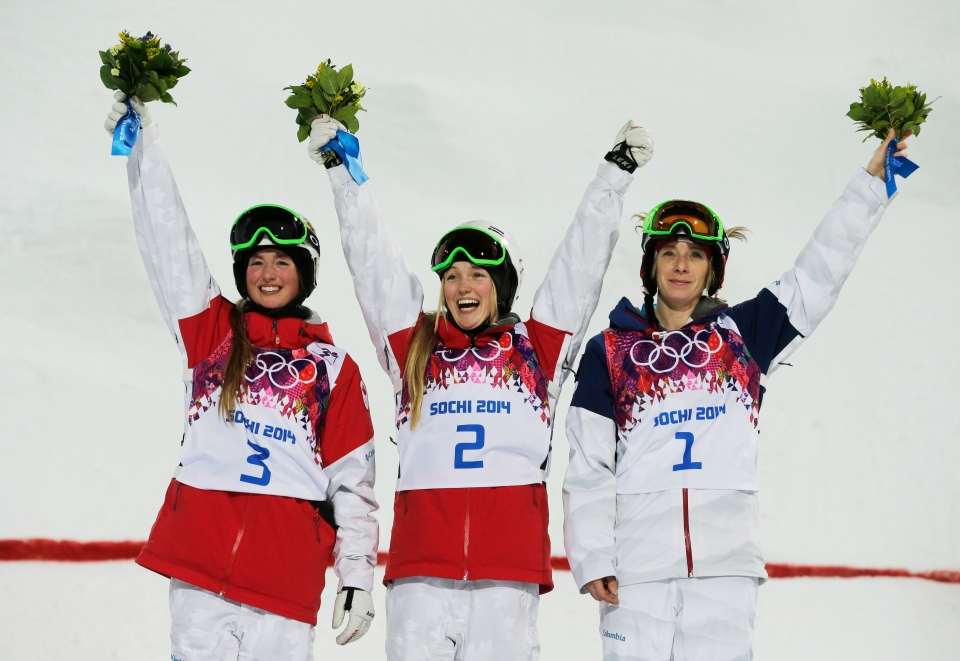 Canada's Justine Dufour-Lapointe, center, celebrates her gold medal in the women's moguls final, with her sister and silver medalist Chloe Dufour-Lapointe, left, and bronze medalist United States' Hannah Kearney, at the Rosa Khutor Extreme Park, at the 2014 Winter Olympics, Saturday, Feb. 8, 2014, in Krasnaya Polyana, Russia. (AP / Andy Wong)