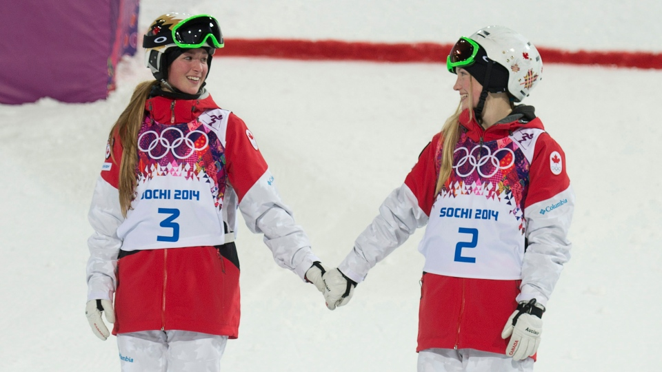 Canada's Justine Dufour-Lapointe and Chloe Dufour-Lapointe holds hands before climbing on the podium after winning the gold and silver medals in the moguls at the Sochi Winter Olympics Saturday February 8, 2014 in Sochi, Russia. (Adrian Wyld / THE CANADIAN PRESS)