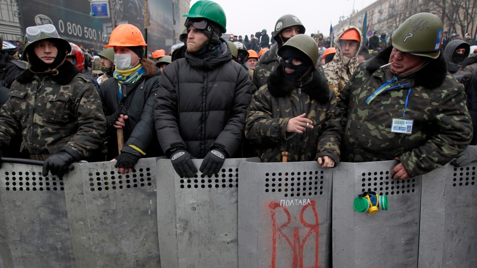 Pro-European Union activists stand in front of a barricade of their tent camp to protect it in downtown Kiev, Ukraine, Saturday, Feb. 8, 2014. Thousands of people angered by months of anti-government protests in the Ukrainian capital converged on one of the protesters' barricades Saturday, but retreated after meeting sizeable resistance. (AP / Sergei Chuzavkov)