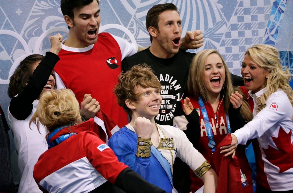 Kevin Reynolds of Canada, centre, reacts as he sits in the results area after competing in the men's team free skate figure skating competition at the Iceberg Skating Palace during the 2014 Winter Olympics in Sochi, Russia on Sunday, Feb. 9, 2014. (AP / David J. Phillip )