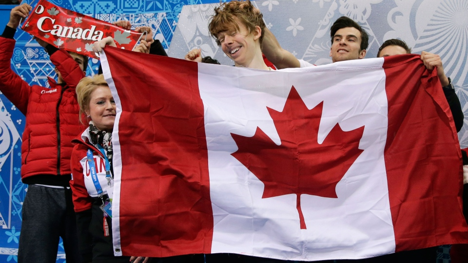 Kevin Reynolds of Canada, centre, and team members react in the results area after he competed in the men's team free skate figure skating competition at the Iceberg Skating Palace during the 2014 Winter Olympics in Sochi, Russia on Sunday, Feb. 9, 2014. (AP / Darron Cummings)
