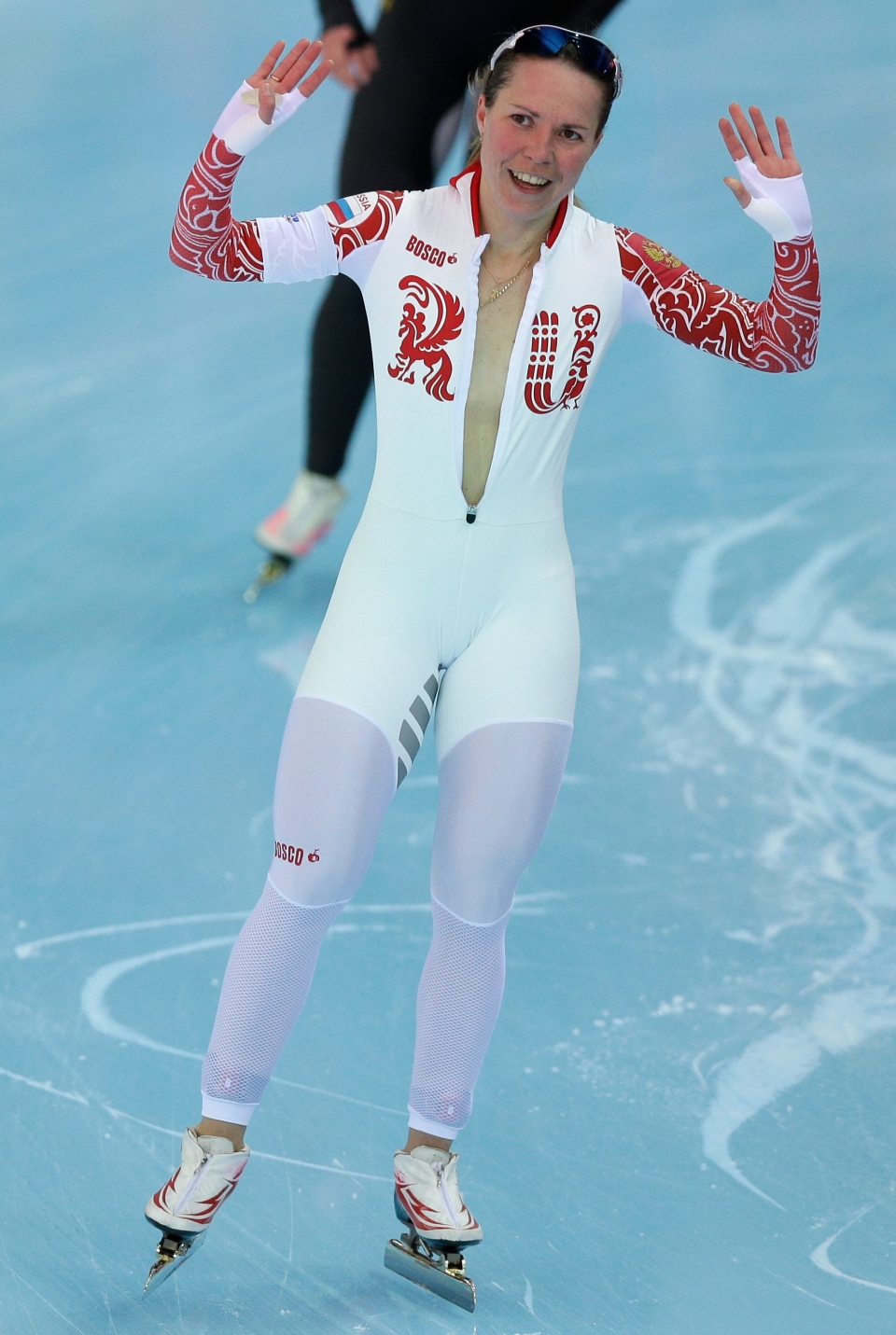 Bronze medallist Olga Graf of Russia celebrates with a wide-open front of her skin suit after the women's 3,000-metre speedskating race at the Adler Arena Skating Center during the 2014 Winter Olympics on Feb. 9, 2014. (AP Photo/Pavel Golovkin)
