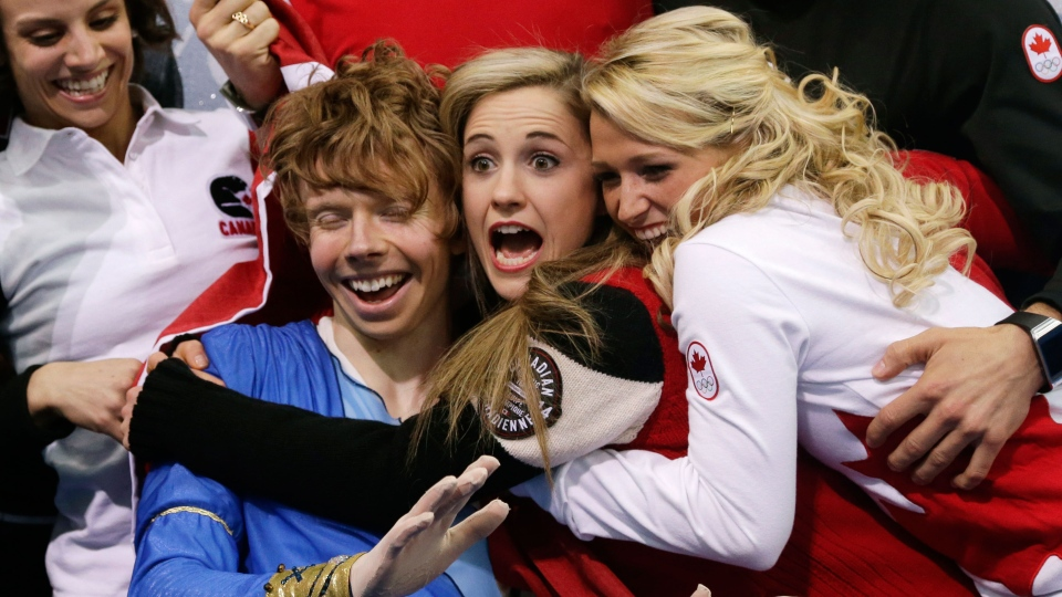 Kevin Reynolds of Canada, left, reacts with fellow team members in the results area after competing in the men's team free skate figure skating competition at the Iceberg Skating Palace during the 2014 Winter Olympics in Sochi, Russia on Sunday, Feb. 9, 2014. (AP / Darron Cummings)