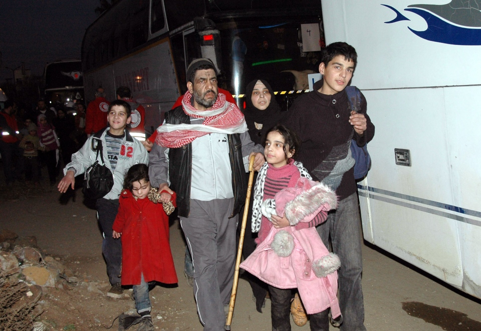 Syrian citizens walk toward a bus to evacuate the battleground city of Homs, Syria on Feb. 9, 2014. (SANA)