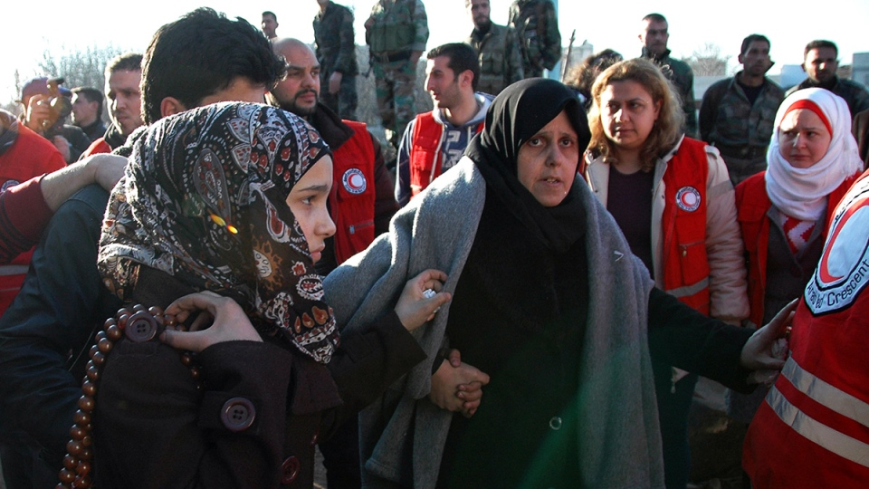 Syrian army soldiers, top background, look on as two women walk towards a bus to evacuate the battleground city of Homs, Syria, Sunday, Feb. 9, 2014. (SANA)