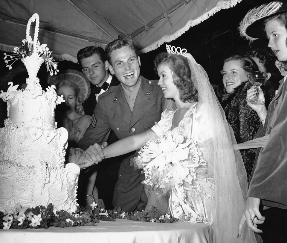 Newlyweds Shirley Temple and Sgt. John Agar Jr. cut their wedding cake beneath a tent on the lawn of the Temple estate on Sept. 19, 1945. (AP Photo)