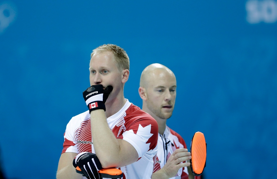 Canada's skip, Brad Jacobs, left, and Ryan Fry, right, wait for their turn to curl during the men's curling competition against Germany at the 2014 Winter Olympics, Monday, Feb. 10, 2014. (AP / Wong Maye-E)