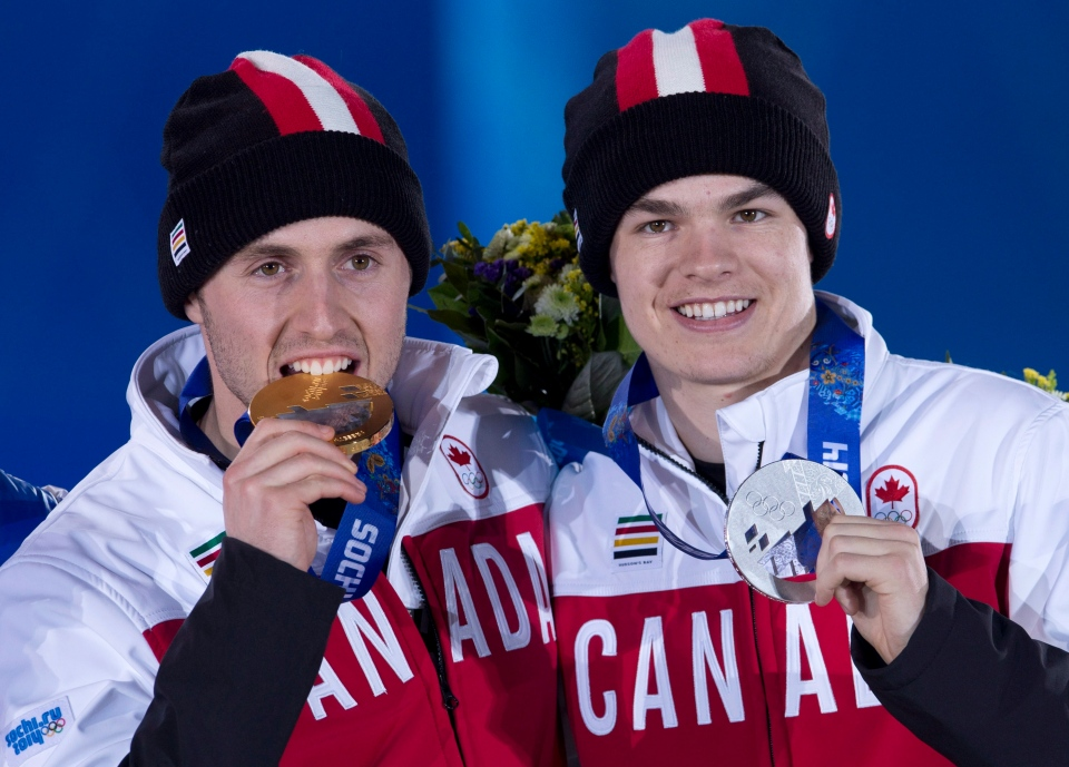 Moguls gold medallist Alex Bilodeau and silver medallist Mikael Kingsbury celebrate during a medal ceremony at the Sochi Winter Olympics on Tuesday, Feb. 11, 2014. (Adrian Wyld / THE CANADIAN PRESS)
