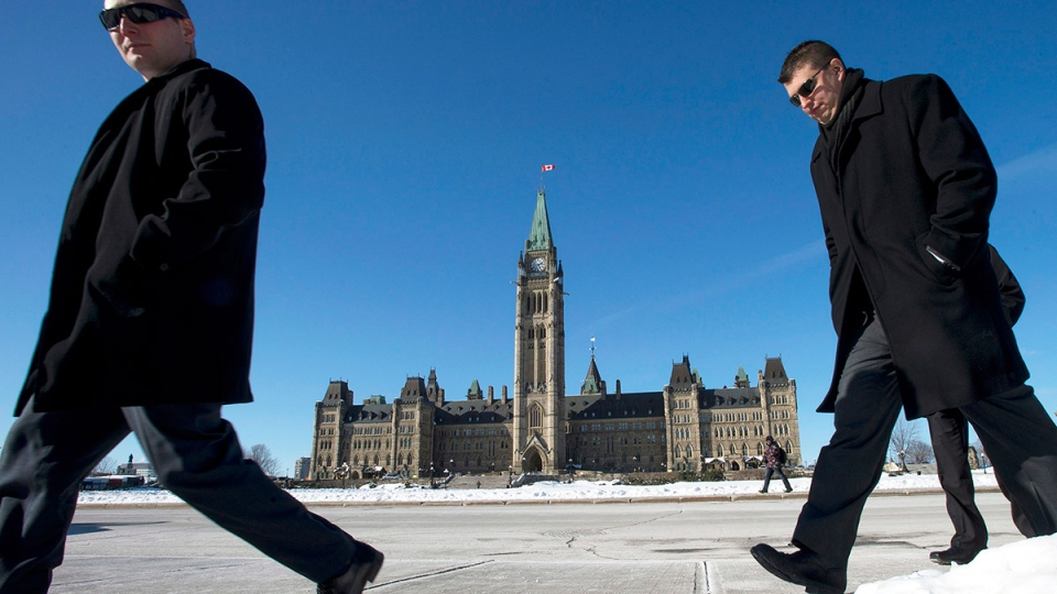 People walk on Parliament Hill as Finance Minister Jim Flaherty prepares to table the budget in Ottawa on Tuesday, Feb. 11, 2014. (Justin Tang / THE CANADIAN PRESS)