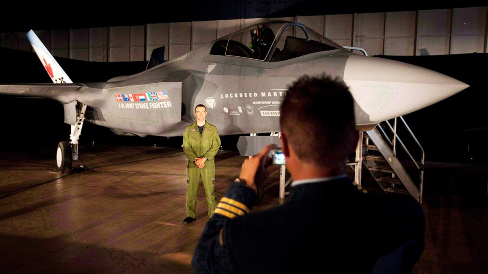 In this file photo, a Canadian Forces pilot has his picture taken in front of a F-35 Strike Fighter prior to an announcement in Ottawa, on July 16, 2010. (Adrian Wyld / THE CANADIAN PRESS)