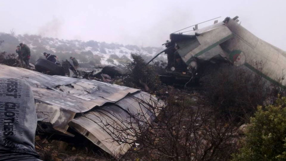 A man watches rescue workers working at the wreckage of Algerian military transport aircraft after it slammed into a mountain in the country's rugged eastern region, Tuesday, Feb. 11, 2014. ( AP / Mohamed Ali)