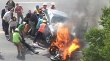 Bystanders rush to drag a young biker out from under a burning car in Utah, Monday, Sept. 13, 2011.