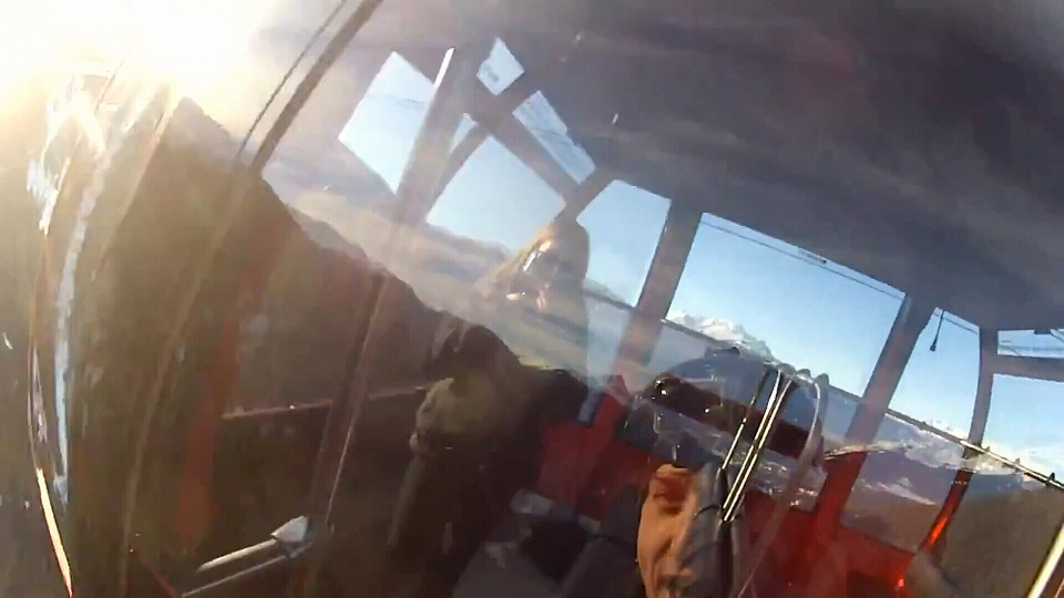 In this still from a YouTube video, a man can be seen in the reflection of a Whistler-Blackcomb Peak 2 Peak gondola car before BASE jumping from the gondola. Whistler RCMP are investigating the video. Feb. 12, 2014. (YouTube)