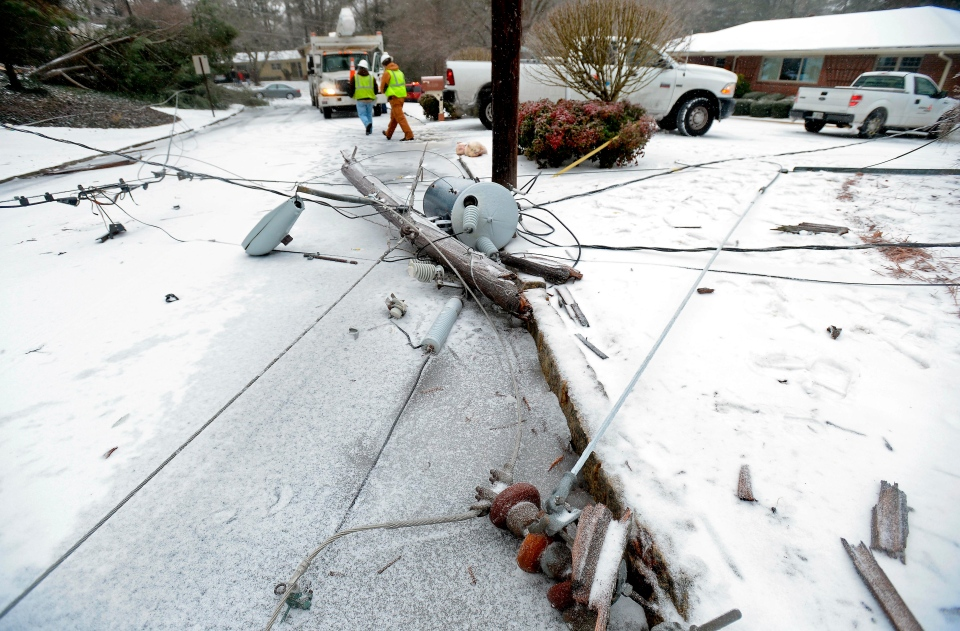 Power company crews work on a downed power line near Emory University after the weight of accumulating freezing rain, sleet and snow toppled a nearby tree that slammed into power poles during a winter storm in Atlanta on Wednesday, Feb. 12, 2014.  (AP / David Tulis)