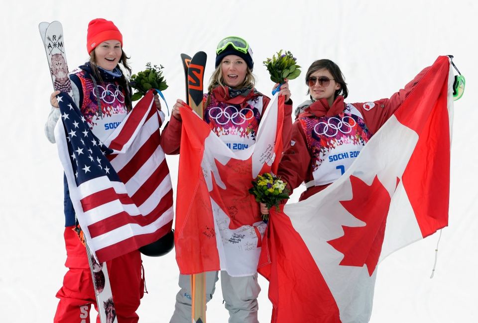 Canada's Dara Howell, center, celebrates on the podium with silver medalist Devin Logan of the United States, left, and Kim Lamarre, right, also of Canada, after Howell took the gold medal in the women's freestyle skiing slopestyle final at the Rosa Khutor Extreme Park at the 2014 Winter Olympics in Krasnaya Polyana, Russia, Tuesday, Feb. 11, 2014. (AP / Andy Wong)