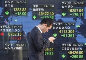 A man walks by an electronic stock board of a securities firm in Tokyo, Tuesday, Jan. 14, 2014. (AP / Koji Sasahara)