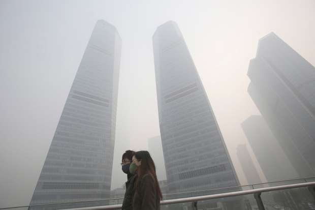 A couple in protective masks walk under haze in Shanghai, China, Friday, Dec. 6, 2013. Shanghai authorities ordered schoolchildren indoors and halted all construction Friday as China's financial hub suffered one its worst bouts of air pollution, bringing visibility down to a few dozen meters and obscuring the city's spectacular skyline. (AP / Eugene Hoshiko)