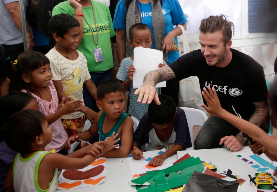 Former England soccer team captain David Beckham interacts with typhoon survivors during his visit to Typhoon Haiyan-hit Tacloban city, central Philippines, Thursday, Feb. 13, 2014. Beckham visited the storm-devastated Philippine city as part of UNICEF's relief efforts. (AP / Bullit Marquez)