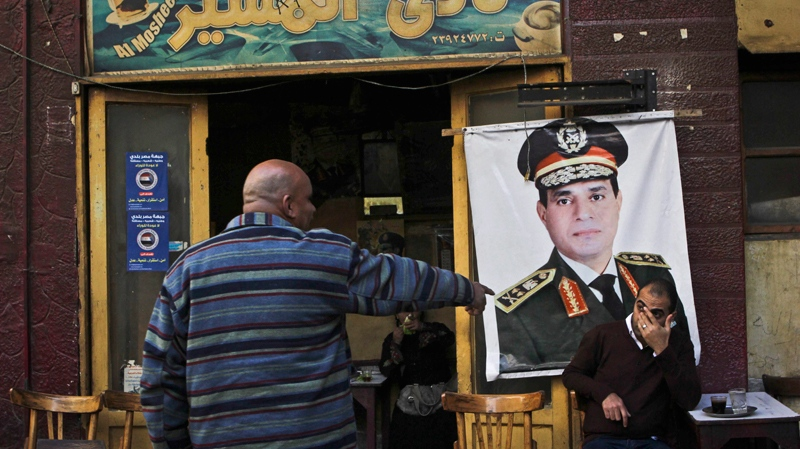 A man sits under a banner with the photo of Defence Minister Gen. Abdel-Fattah el-Sissi at the 'Al Mosheer Cafe' or 'Marshal Cafe' in Cairo, Egypt, Tuesday, Jan. 27, 2014. (AP / Mohammed Abu Zaid)