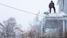 Man clears snow off roof after U.S. winter storm