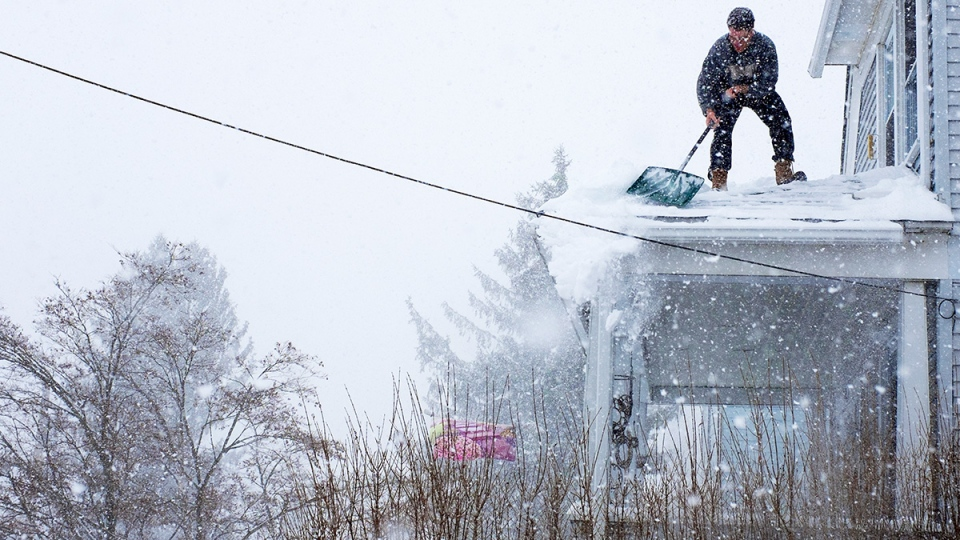 Chris Starace works to clear snow from his home's roof in Ossining, N.Y. on Thursday, Feb. 13, 2014. (AP / Craig Ruttle)