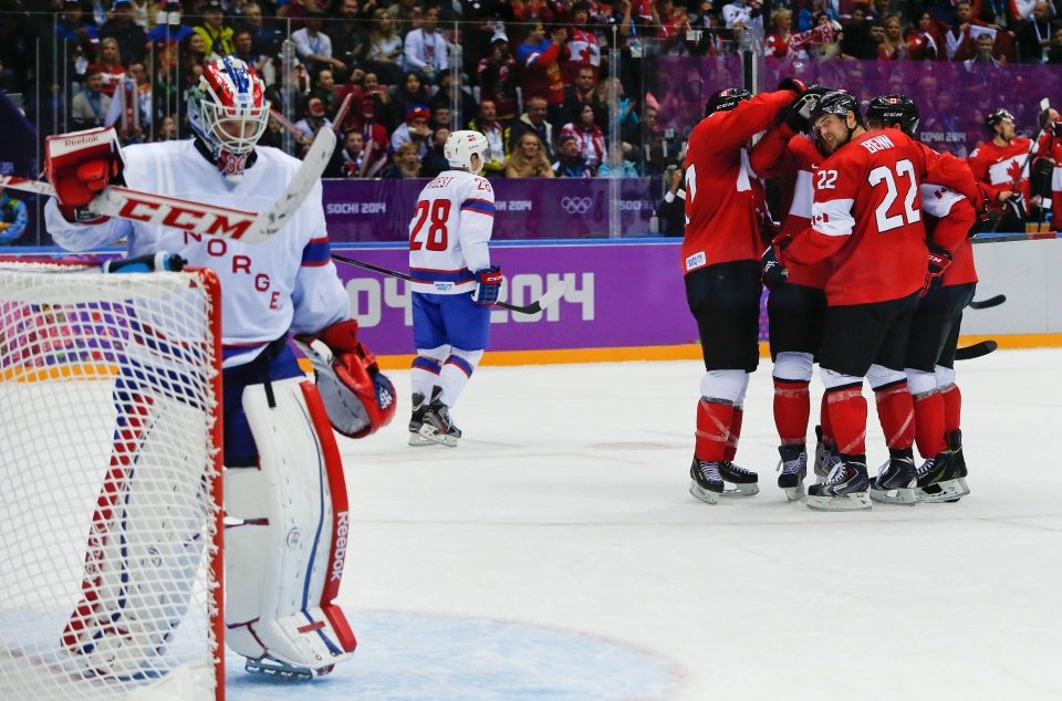 Canada forward Benn Jamie looks to Norway goaltender Lars Haugen after teammate Canada forward Patrice Bergeron scored a goal in the second period of a men's ice hockey game at the 2014 Winter Olympics, Thursday, Feb. 13, 2014, in Sochi, Russia. Canada beat Norway 3-1. (AP / Julio Cortez)
