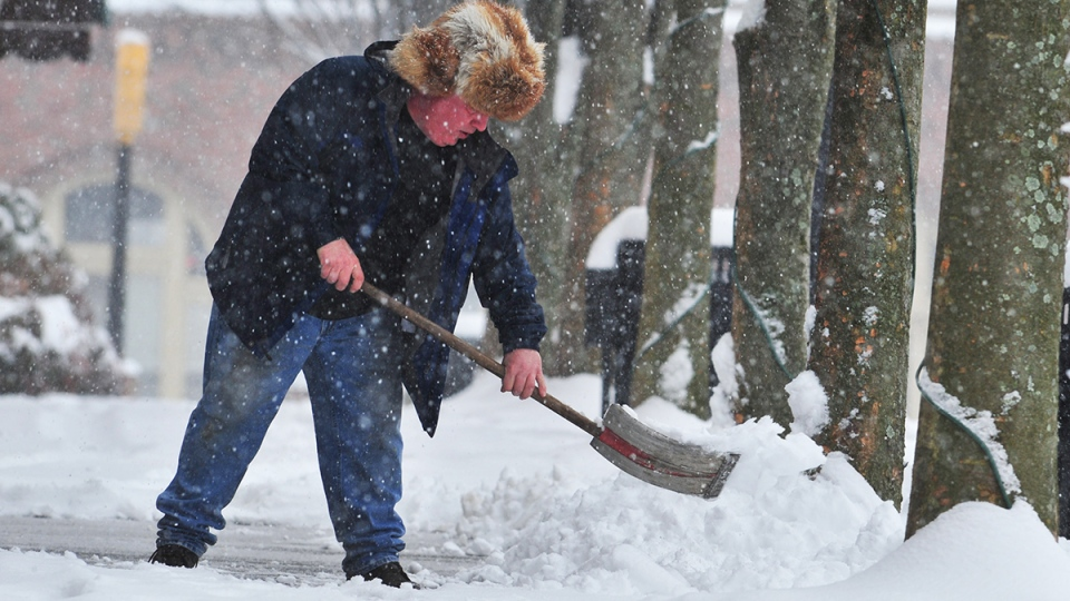 Tray Kistner shovels snow off sidewalk along Broad Street in Kingsport Tenn., Thursday Feb. 13, 2014. (AP / The Kingsport Times-News, David Grace)