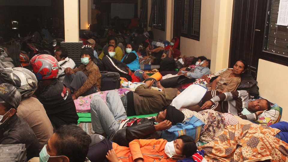 Villagers sleep at a temporary shelter after they were evacuated from their homes on the slope of Mount Kelud in Kediri, East Java, Indonesia, Friday, Feb. 14, 2014. (AP Photo)