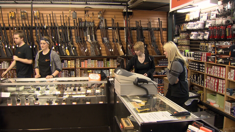 Staff stand behind display cases at Wanstalls, a hunting and sporting goods store in Maple Ridge, B.C. Feb. 13, 2014. (CTV)