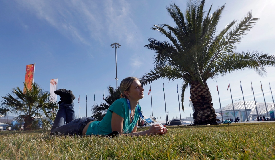 Oxsana Kharitonova lyes on the grass while posing for a photograph with friends on a sunny warm day at the 2014 Winter Olympics in Sochi, Russia Wednesday, Feb. 12, 2014. (AP / David J. Phillip )