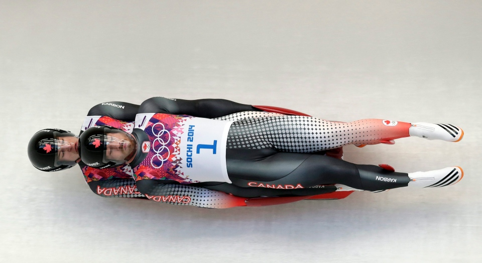 The doubles team of Tristan Walker and Justin Snith from Canada speeds down the track in their first run during the men's doubles luge at the 2014 Winter Olympics in Krasnaya Polyana, Russia, Wednesday, Feb. 12, 2014. (AP / Michael Sohn)