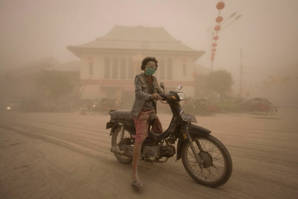 A women rides a motor bike on a street covered with volcanic ash from an eruption of Mount Kelud, in Solo, Indonesia, Friday, Feb. 14, 2014. (AP / Hafidz Novalsyah)