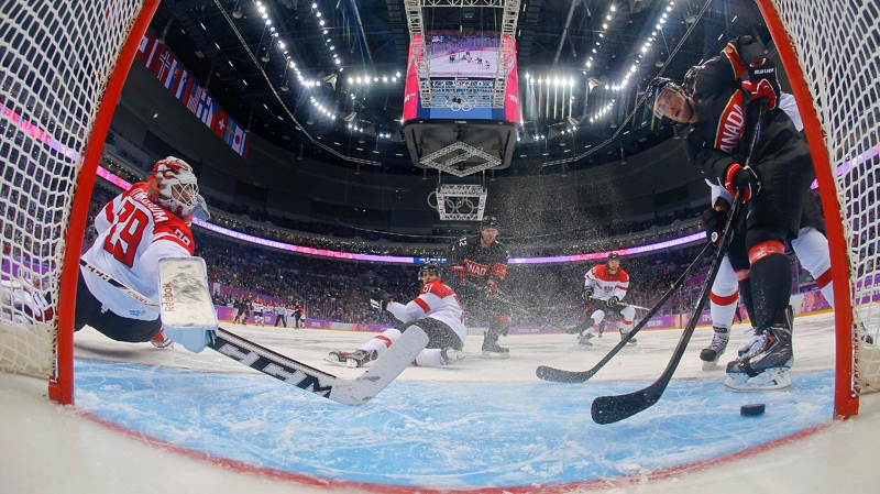 Canada forward Jeff Carter scores against Austria goaltender Bernhard Starkbaum in the second period of a men's ice hockey game at the 2014 Winter Olympics, Friday, Feb. 14, 2014, in Sochi, Russia. (AP / Mark Blinch, Pool)