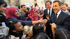 French President Nicholas Sarkozy, right, and British Prime Minister David Cameron, second from right, greet people gathered in a square during their visit to Benghazi, Libya, Thursday, Sept. 15, 2011. (AP / Philippe Wojazer)