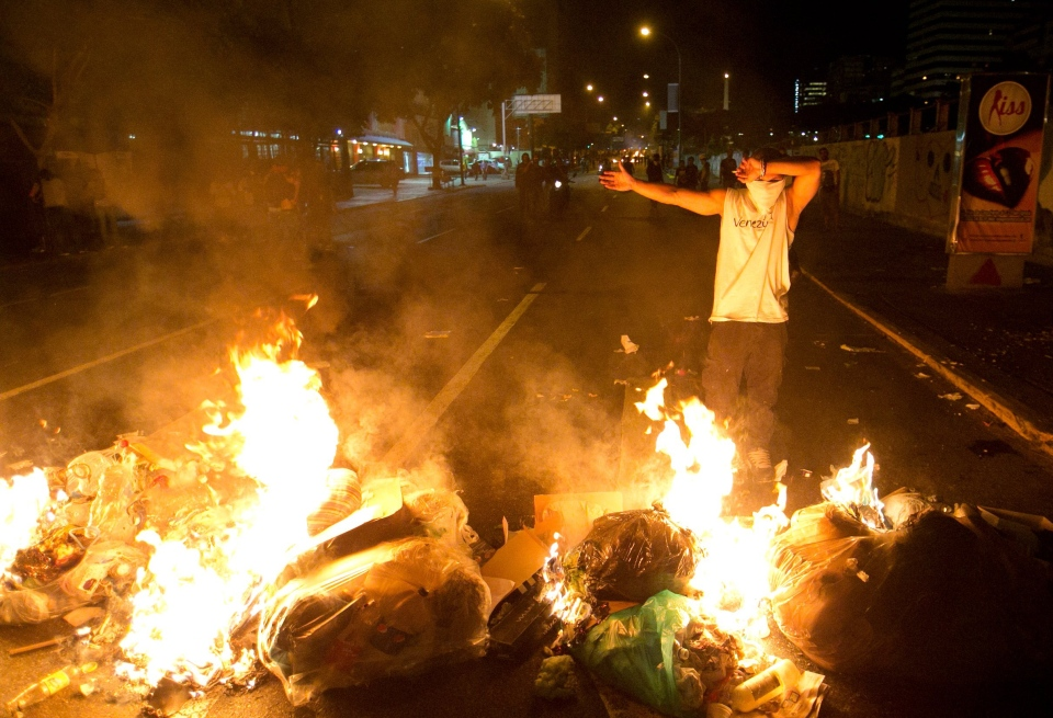 A demonstrator stands in front of a burning barricade during a protest in Caracas, Venezuela, Friday, Feb. 14, 2014. (AP / Alejandro Cegarra)