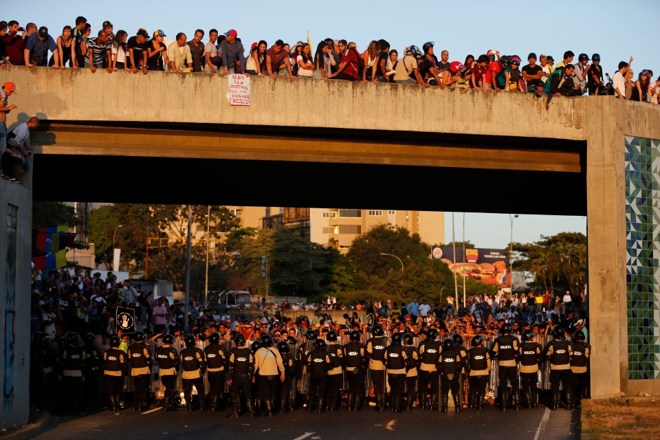 Demonstrators stand on a bridge and another group before a cordon of riot police blocking passage to the main highway during a protest in Caracas, Venezuela, Friday, Feb. 14, 2014. (AP / Fernando Llano)
